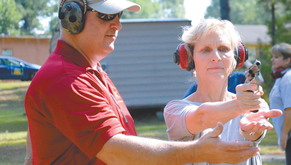 The Pike County Sheriff's Office offered a gun safety class for women. Above, Sgt. Henry Wentland shows Kathy Pugh how to support her hand for a steady shot. Below right, Wentland runs drills with Pugh and Michele Seepersad to get them used to shooting a moving target and reacting quickly. The class included a lesson on rifles, below left. MESSENGER PHOTOS | MONA MOORE