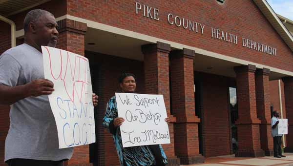 Above, Larry and Marine White hold signs in protest in front of the Pike County Health Department Monday afternoon. They were part of a group protesting the warrant for the arrest of Bishop Ira McCloud, of the Jesus Christ Church of God the Bibleway. McCloud's arrest was related to a septic tank issue on the church's property. (Messenger Photo / April Garon)