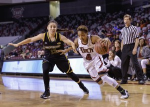 Troy University Ashley Beverly-Kelley drives past a Southeastern Louisiana defender in the Trojans' Nov. 21 matchup with the Lady Lions. Below: Ronita Garrett shoots over a defender.