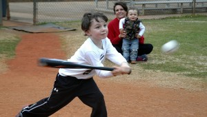 "Ridge Hicks, age four, swings hard and sometimes he misses, but ""that's baseball."" His mom, Shannon Hicks and brother, Baylor, made up the cheering section at Monday's practice."