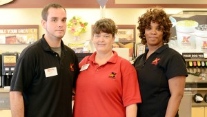 Messenger Photo/Courtney Patterson Kangaroo Express's manager, Kimberlee Messer (center), gives free coffee to all firefighters and police officers as a thank you for their service. Pictured are Scott Blocher, assistant manager (left) and Miss Tee, food manager (right).