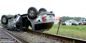 Messenger Photo/Scottie Brown A woman hydroplaned on Alabama Highway 29 North, and the vehicle flipped and landed on the train tracks. She was ejected from the vehicle while the car rolled. The woman was transported to the hospital with head injuries, according to an eye witness.