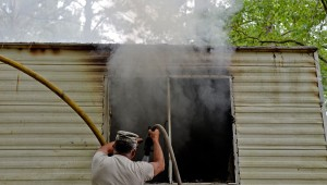 Messenger photo/Thomas Graning Firefighters work to extinguish a fire in a trailer at Clearwater Mobile Home Park in the Hamilton Crossroads community of Pike County. Firefighters responded to a fire in a rear room of the home about 10:35 a.m. The fire was contained to the room, though the rest of the trailer suffered smoke and water damage. Firefighters from Hamilton Crossroads, Brundidge, Pike County Fire Rescue and Troy Fire Department responded to the call.