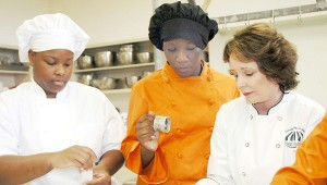 Sister Schubert demonstrated the art of making rols to Jaquetta Brundidge and Ebony Williams. Schubert visited the Culinary Arts Academy at Charles Henderson High School Tuesday.