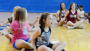 Messenger photo/Courtney Patterson Troy University cheerleaders play Ships and Sailors with the campers at the Troy Parks and Recreation summer camp on the kick-off day Monday.
