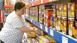 MESSENGER PHOTO/COURTNEY PATTERSON Michele Rushing, manager at Crazy Bill's Fireworks on Elba Highway, stocks more Roman Candle fireworks in preparation for the holiday this weekend.
