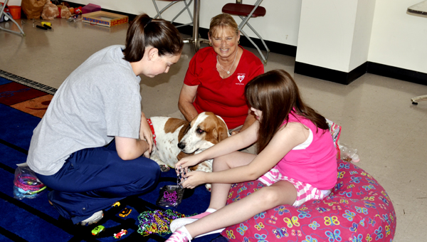 Raqual Cooper plays dress up with Piglet the dog as a part of therapeutic services provided by the Exceptionally Special Youth Day Camp program. Piglet is a trained therapy dog with the Dogs on Call program from Montgomery. MESSENGER PHOTO/QUINTA GOINES