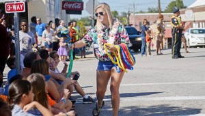 MESSENGER PHOTO/COURTNEY PATTERSON Charles Henderson High School marched in the annual CHHS Homecoming Parade Friday afternoon in Downtown Troy. A CHHS senior passes out lays to the spectators, so they can join in with the seniors' Hawaiian theme.
