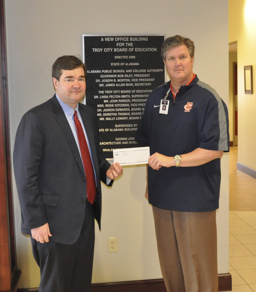 Troy Mayor Jason Reeves presents Troy City Schools Superintendent Dr. Lee Hicks a check for more than $15,000 as part of the SEAGD 'Give Back to Schools' program.