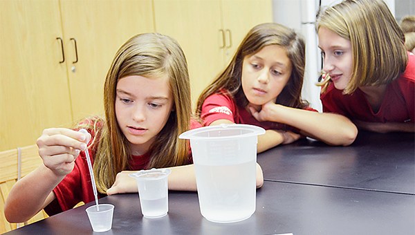 Students attended the 14th Annual Groundwater Festival at Troy University. PLAS students, from left, Anna Kilcrease, Kate Nelson, and Britton Paul, determined the amount of surface water, ground water and glacier and ice caps that make up their groundwater. Below, Dr. Neil Billington tops an edible aquifer with chocolate syrup, representing oil.