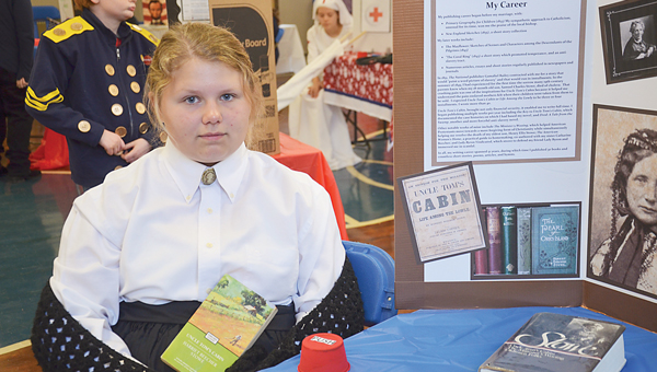 """The auditorium at Banks School was transformed into a wax museum by the school's sixth-grade students this week. The wax museum was a culminating activity for the students' study of the Civil War. Annabella Earles, above, was fascinated by the writings of Harriet Beecher Stowe, especially """"Uncle Tom's Cabin."""" However, she learned the author wrote several other books including children's stories."""