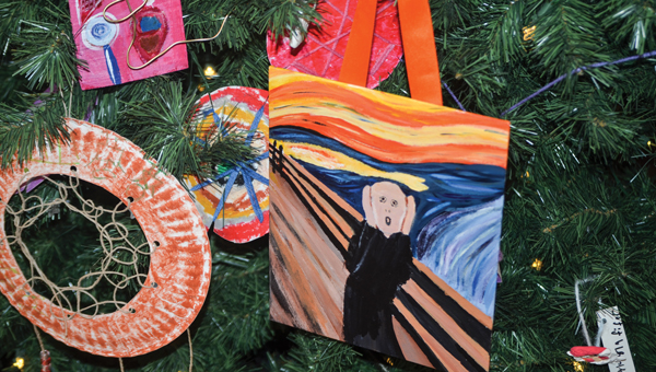 """Banks students decorated a tree with lightbulb-inspired ornaments for one of the themed trees on display now at the Johnson Center for the Arts. Other trees are decorated with replicas of famous paintings includes """"The Scream"""" originally painted by Edvard Munch."""