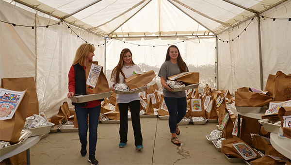 Kelly Sanders, above left, worked with volunteers to help prepared and deliver more than 400 turkey meals to hungry families throughout Pike County on Thursday. Sanders spearheads the annual Turkeys from Heaven program, which took place on Thursday.