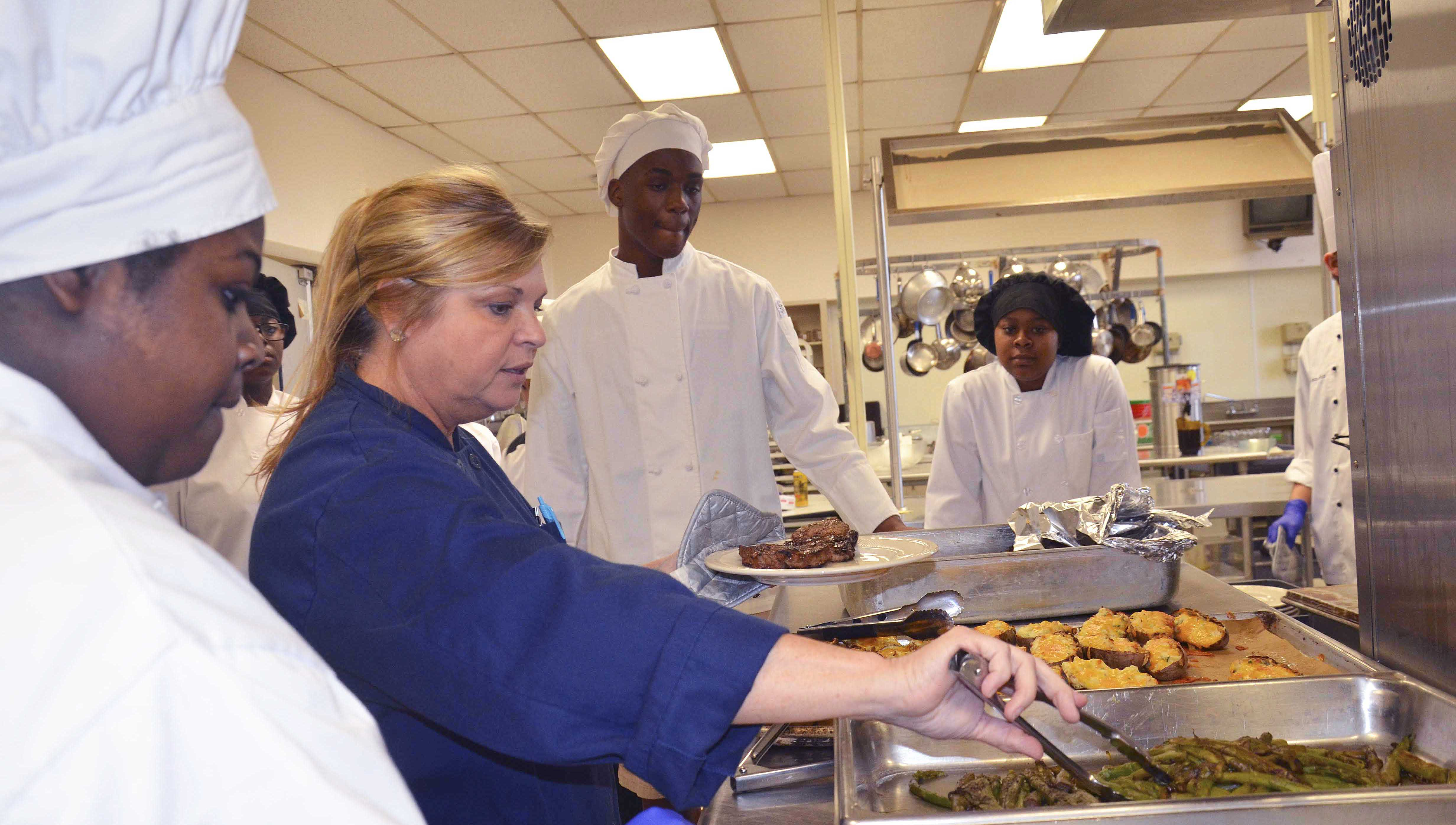 Students at the Culinary Arts Academy prepared lunch for members of the Troy City Board of Education and the Troy City Council Wednesday at the Academy building. The students also prepared homemade dressing, rolls and New York-style cheesecake. Inset: Members of the Troy City Council, Wanda Moultry, Stephanie Baker, Greg Meeks and Marcus Paramore enjoyed the lunch in their honor.
