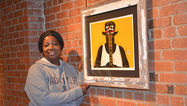 """The Johnson Center for the Arts is featuring the artwork of two African American women, local artist Belinda Harrison and Birmingham artist Debra Riffe, in a duo show through February. Riffe is well known for her wood and linoleum block prints. Harrison is beginning a career as a painter. Mary Hobdy is pictured with Riffe's """"Behind the Music"""" block print."""