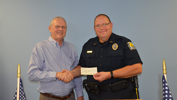 Troy Exchange Club President Jerry Beckett presented Troy Police Chief Randall Barr with a check for $500 at the club's Thursday meeting. The funds will be used to purchase school crossing signs. Barr was the guest speaker at the luncheon meeting.